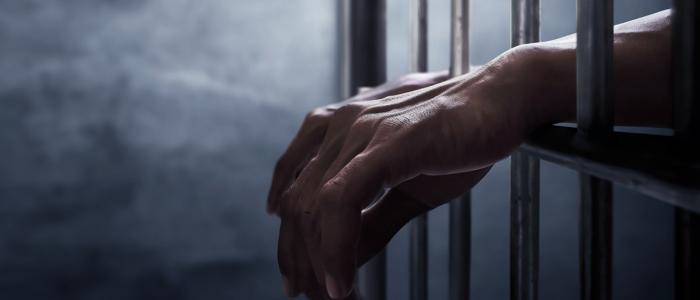 Hands resting on prison bars