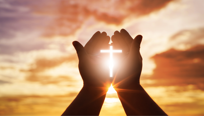 Hands holding a shining cross