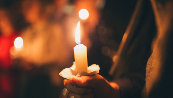 A hand holding a candle.