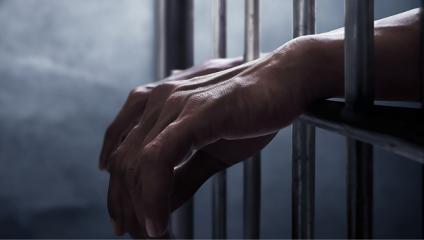 Hands resting on prison bars