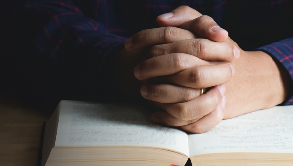 Hands resting on Bible